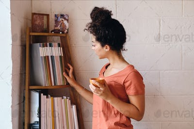 Young beautiful woman in T-shirt holding cup of coffee dreamily choosing book from bookshelf