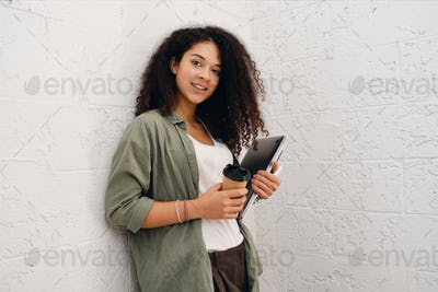 Cute curly woman in khaki shirt holding laptop and coffee dreamily looking in camera