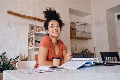 Cute smiling student girl sitting at the desk with laptop and coffee joyfully looking aside studying
