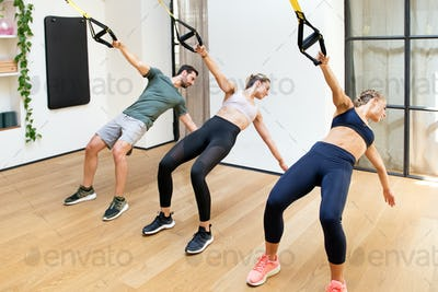 Three people training power pull with trx at gym