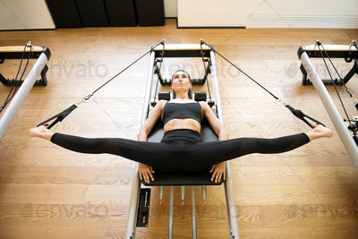 Woman on reformer bed doing hip opening exercises