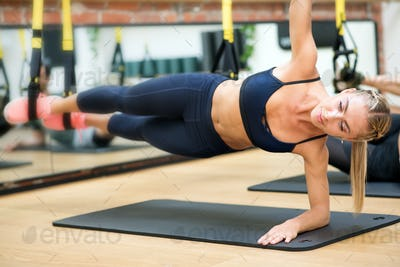 Woman doing suspended elbow side plank with trx