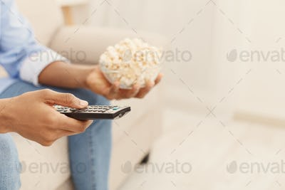 Man holding tv remote controller and popcorn in hands