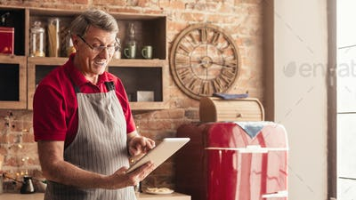 Positive senior man browsing on digital tablet in kitchen