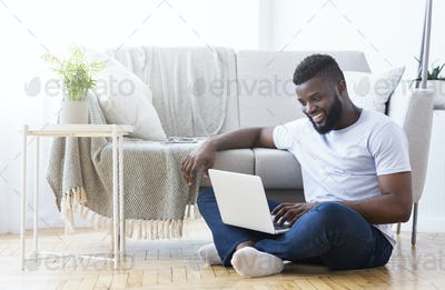 African american guy playing video game on laptop