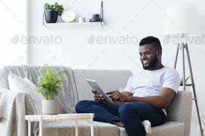 African-american man using digital tablet at home