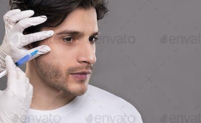 Millennial man getting hyaluronic collagen injection near eyes
