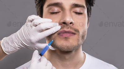 Young male patient receiving botulinum injection in lips