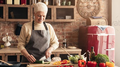 Caring grandmother preparing healthy lunch for family at kitchen