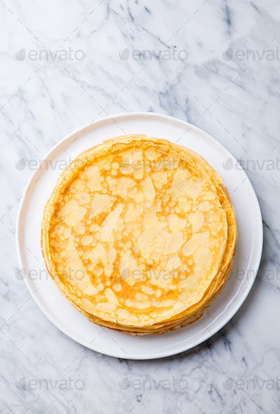 Crepes, Thin Pancakes on a White Plate. Marble Background. Copy Space. Top view.