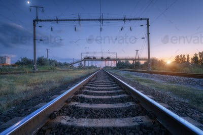 Summer rural industrial landscape with railway station at sunset