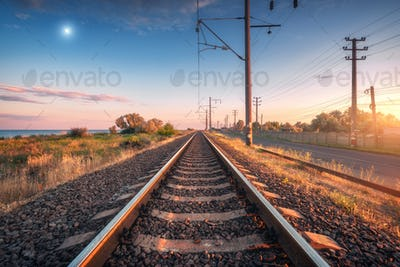 Railroad and blue sky with moon at sunset in summer