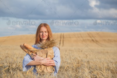 Redhead woman with bakery products in ripe wheat field