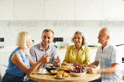Mature Friends Gathered at Kitchen Table