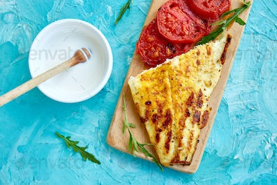 Grilled pike fillet with tomatoes on wooden board