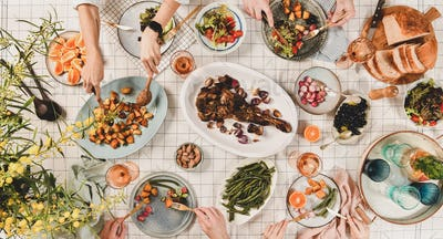 Peoples hands over table with meat, salads, wine, wide composition
