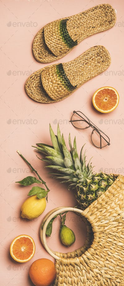 Summer apparel set and fruits over pink background, vertical composition