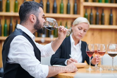 Young elegant sommelier tasting red wine from one of glasses