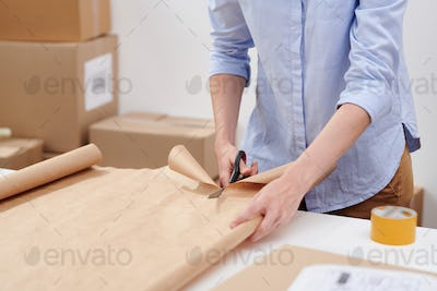 Young casual female worker of online shop office cutting wrapping paper