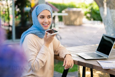 Happy girl in hijab recording voice message on smartphone in park
