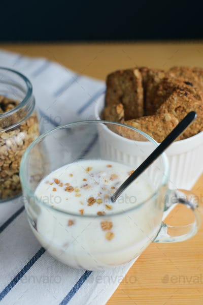 milk and cereals flakes in glass cup with granola and wholegrain cookies