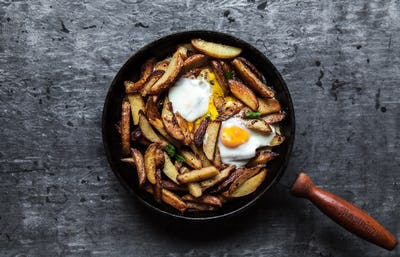 Fried potatoes and eggs in a pan close-up. horizontal