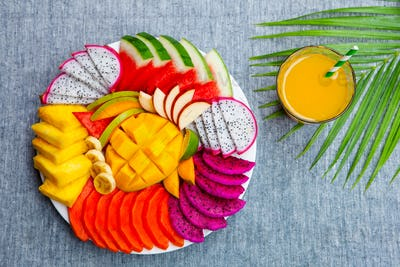 Tropical Fruits Assortment on a White Plate with Fresh Juice, Textile Grey Background. Top View