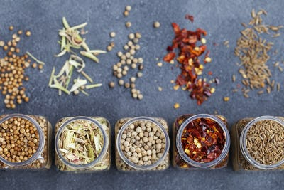 Assortments of Spices in Jars on Grey Stone Background. Top view. Copy space.