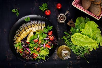 Smoked mackerel and fresh salad on dark background. Top view