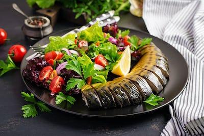 Smoked mackerel and fresh salad on dark background.