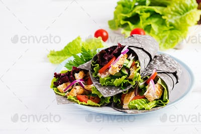 Tortilla with added ink cuttlefish wraps with chicken and vegetables on white background.