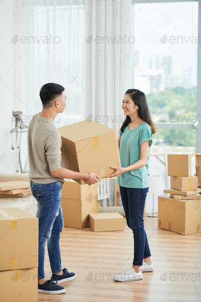 Couple with cardboard box at home