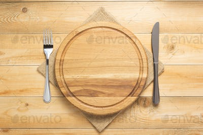 pizza cutting board and napkin at rustic wooden table