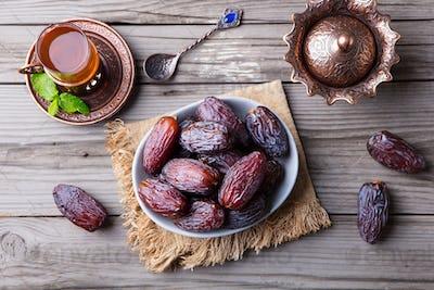 Fresh Medjool Dates in a Bowl with Tea. Ramadan Kareem. Grey Wooden Background.. Top View.