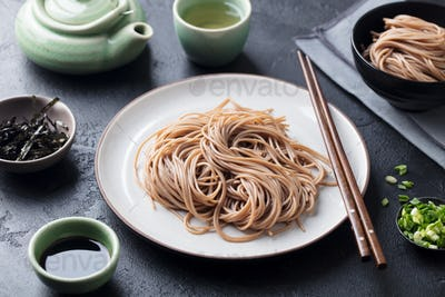 Soba Noodles with Sauce and Garnishes. Japanese Food. Black Slate Background. Close up.