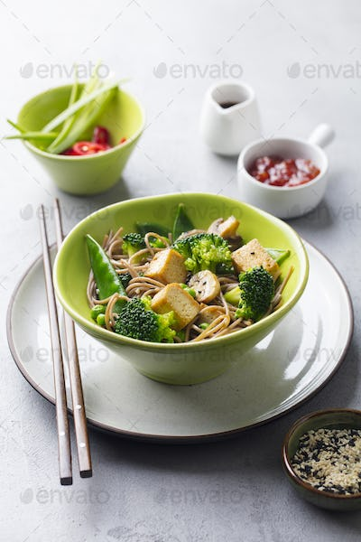 Soba Noodles with Vegetables and Fried Tofu in a Bowl. Grey Background.