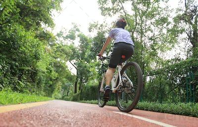 Woman cyclist riding Mountain Bike on bike path in park
