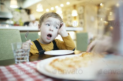 Young boy yawning as he waits to be fed