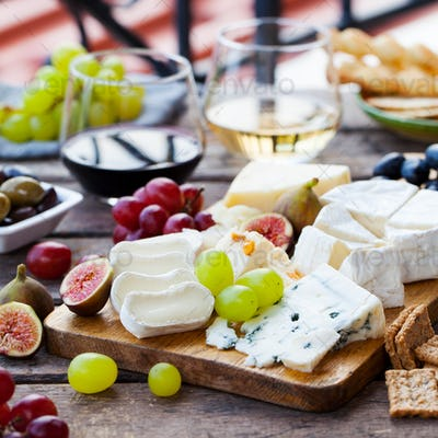 Cheese and Fruits Assortment on Cutting Board with Red, White Wine on Wooden Background. Copy Space.