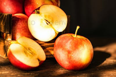 Apples whole and cut in halves on wooden surface