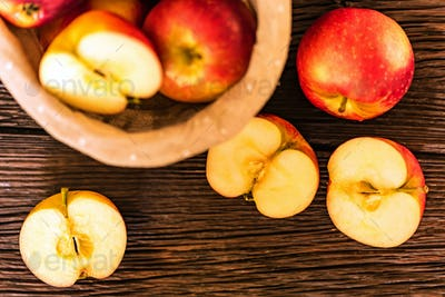 Red juicy apples and halves in basket top view