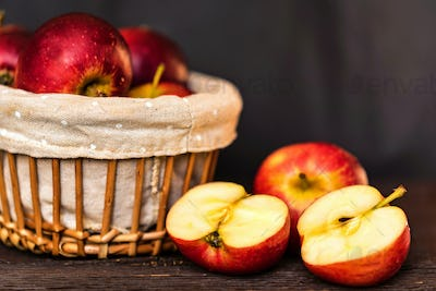 Red juicy apples and halves in basket close