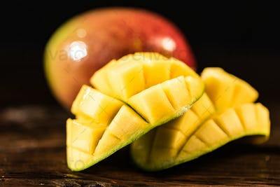 Whole and cut mango on a dark wood background