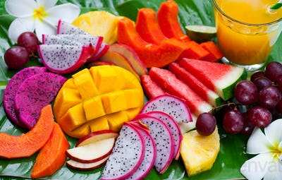 Tropical Fruits Assortment with Fresh Juice, Palm Leaf Background. Top View. Close up.