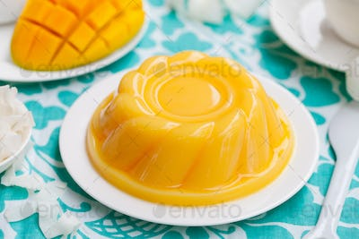 Mango Pudding, Jelly, Dessert on White Plate with Fresh Fruit. Colorful Textile Background.