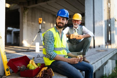Happy mature and young engineer, architect, worker sitting at building site and resting