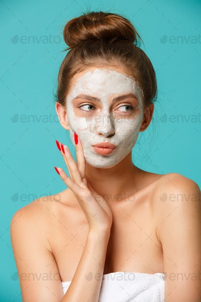 Beauty treatment - woman applying clay face mask