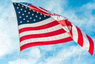 American flag waving in blue cloudy sky