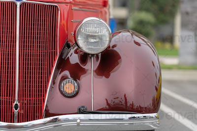 Close up of vintage burgundy car bumper and lamps