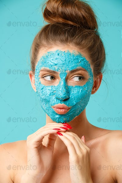 Beauty treatment - woman applying clay face scrub mask